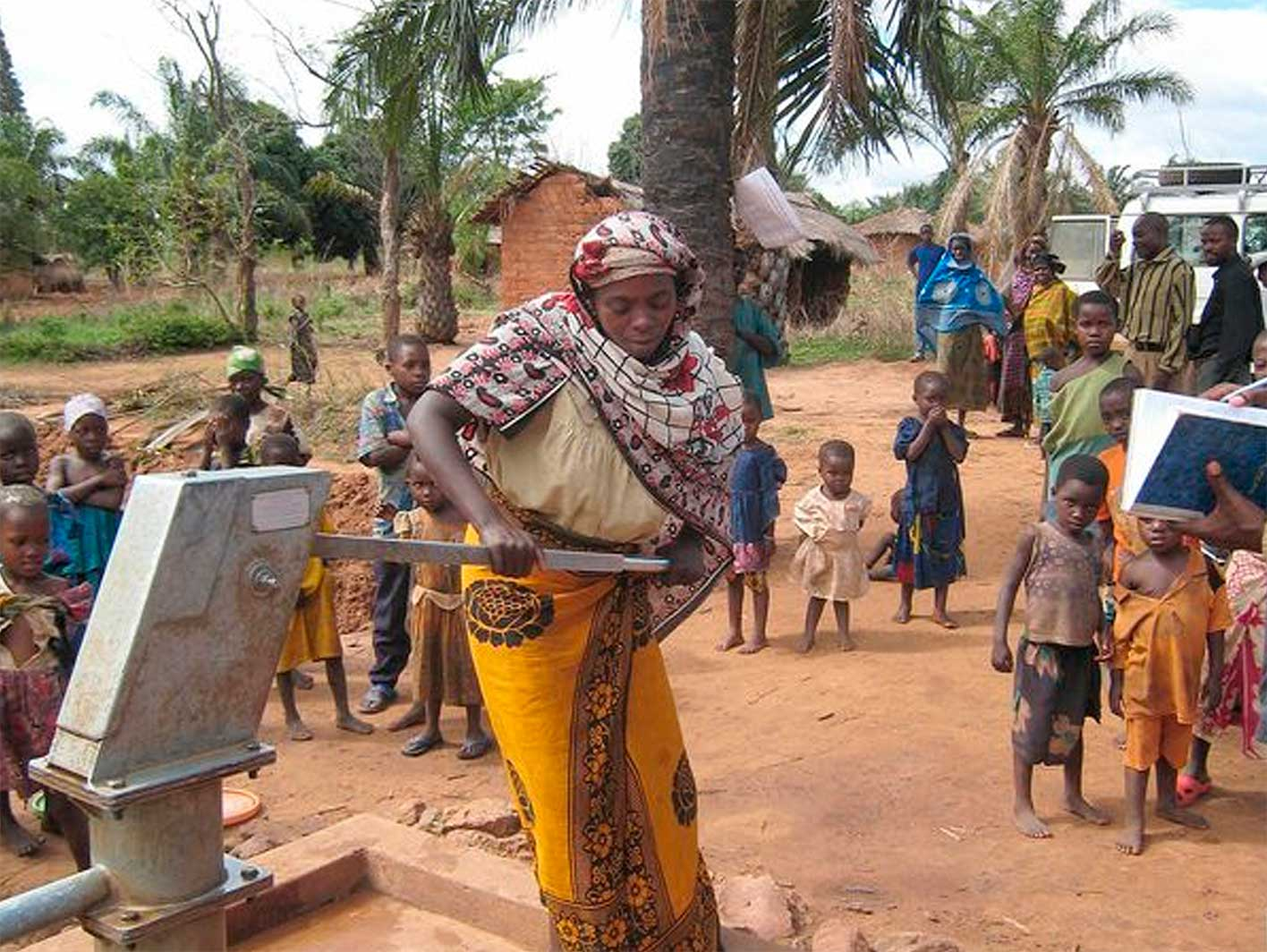 Afrikanische Frau pumpt Wasser aus einem Brunnen