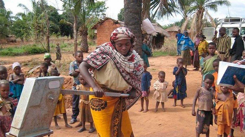 Afrikanische Frau pumpt Wasser aus Brunnen