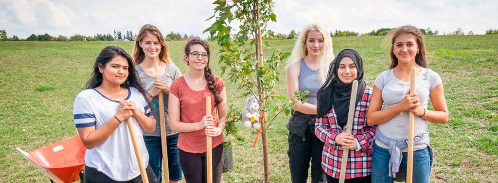 Roots & Shoots Mitglieder pflanzen einen Baum