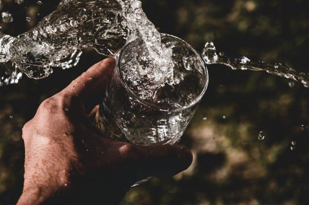Ein Mensch hält ein Glas frisches Quellwasser